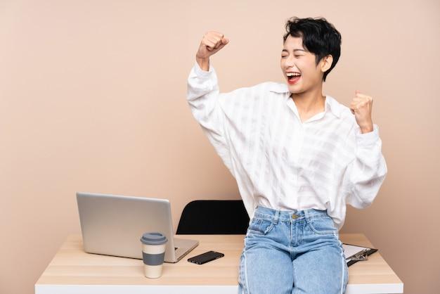 Donna asiatica di giovani affari nel suo luogo di lavoro che celebra una vittoria