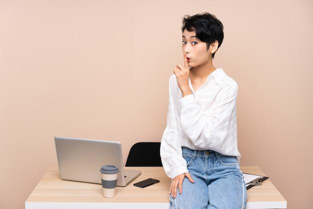 Donna asiatica di giovani affari nel suo luogo di lavoro che fa gesto di silenzio