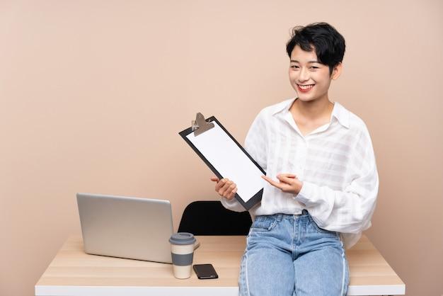 Donna asiatica di giovani affari nel suo luogo di lavoro