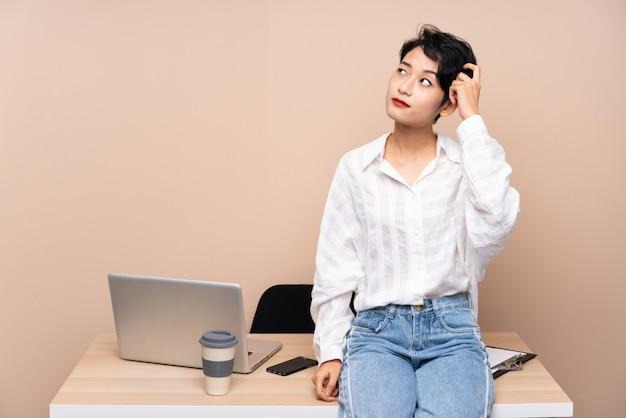 Donna asiatica di giovani affari nel suo posto di lavoro che ha dubbi e con l'espressione confusa del fronte