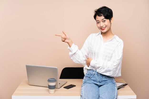 Donna asiatica di giovani affari nel suo posto di lavoro che indica dito il lato
