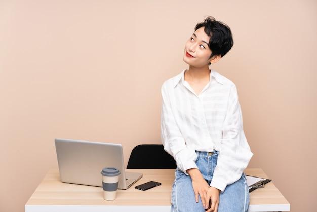 Donna asiatica di giovani affari nel suo posto di lavoro che ride e che osserva in su