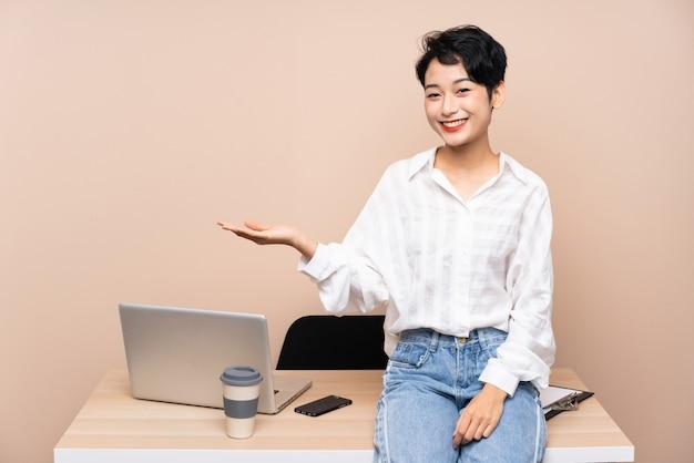 Donna asiatica di giovani affari nel suo posto di lavoro che tiene qualcosa