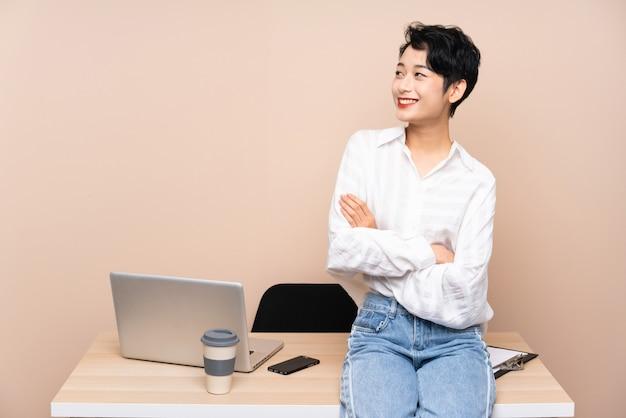 Donna asiatica di giovani affari nella sua risata del posto di lavoro