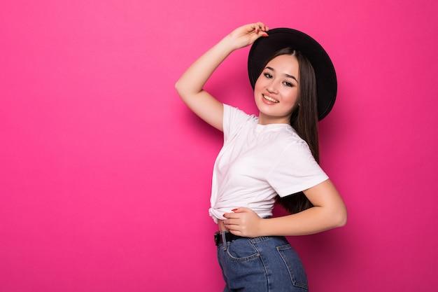 Donna asiatica di pensiero felice e allegra sulla parete rosa.