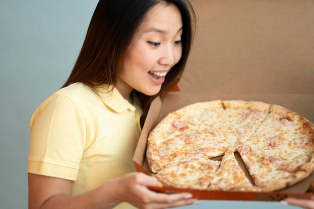 Donna asiatica di smiley che esamina una pizza deliziosa
