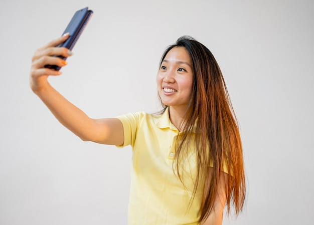Donna asiatica di smiley che prende un selfie