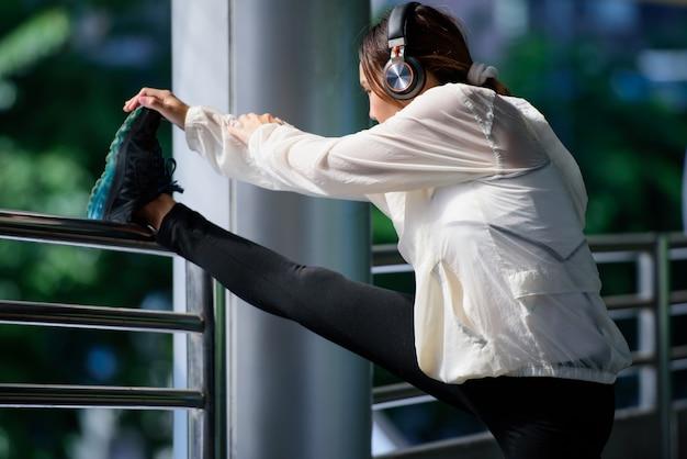 Donna asiatica di sport che allunga le gambe e musica d'ascolto con la cuffia all'aperto.
