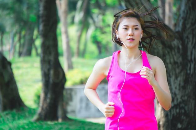 Donna asiatica di sport che pareggia, che corre nel parco