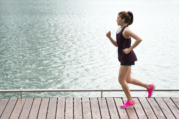 Donna asiatica di sport che pareggia sull'orlo del lago in parco