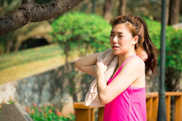 Donna asiatica di sport con l'asciugamano per esercizio nel parco