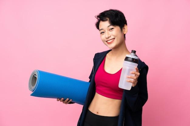 Donna asiatica di sport giovane sopra la parete rosa isolata con la bottiglia di acqua di sport e con una stuoia