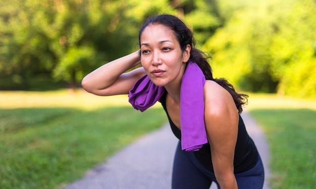 Donna asiatica di sport stanco con l'asciugamano al parco