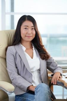 Donna asiatica elegantemente vestita sicura che si siede nella sedia esecutiva in ufficio