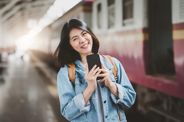 Donna asiatica felice alla stazione ferroviaria
