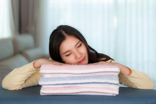 Donna asiatica felice che dorme sui vestiti piegati puliti a casa.