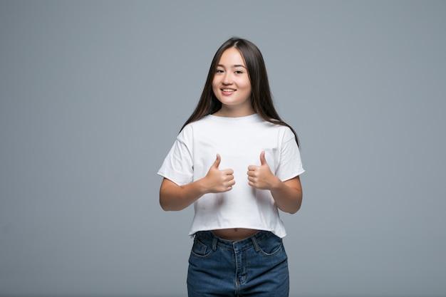 Donna asiatica felice che mostra pollice su e che esamina la macchina fotografica sopra fondo grigio