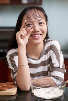 Donna asiatica felice che posa nella cucina e che guarda attraverso la taglierina a forma di cuore del biscotto