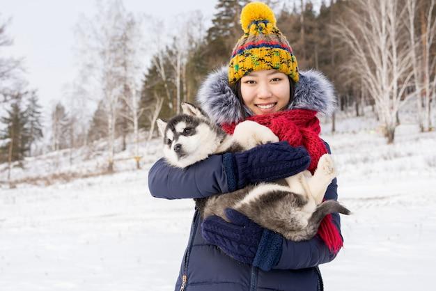 Donna asiatica felice che propone con il cucciolo
