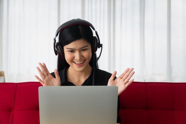 Donna asiatica felice che si siede su un sofà e su una videoconferenza con un socio commerciale