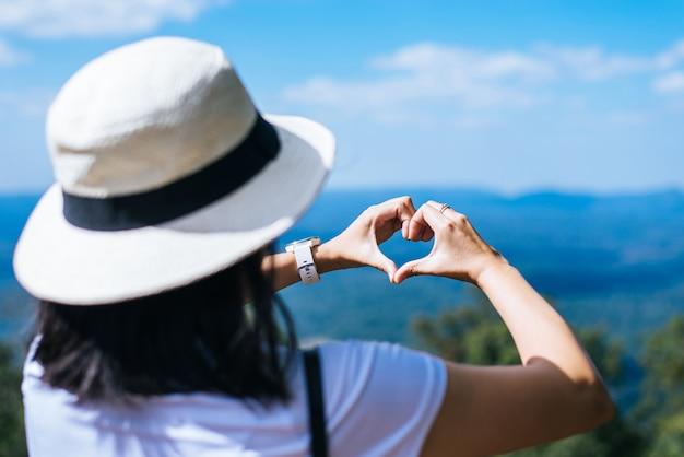 Donna asiatica felice che sta e che mostra a forma di cuore delle mani alla natura, tempo libero, pensiero positivo