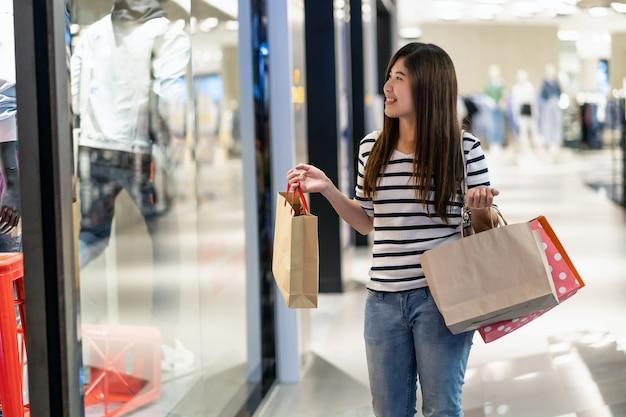 Donna asiatica felice che tiene il sacchetto della spesa e che cerca i nuovi vestiti di modo attraverso il gla