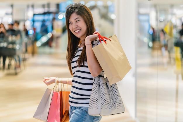 Donna asiatica felice che tiene il sacchetto della spesa e che cerca i nuovi vestiti di modo