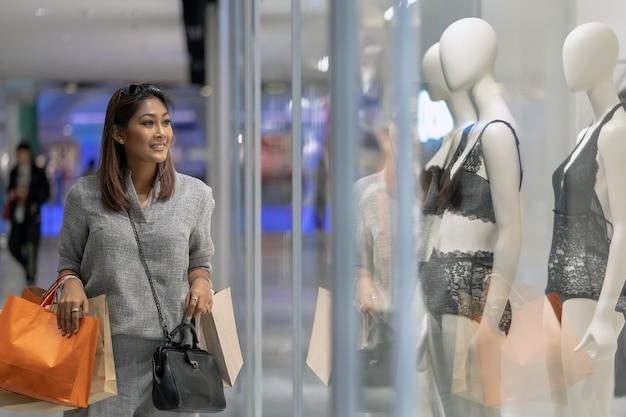 Donna asiatica felice che tiene il sacchetto della spesa e guardare