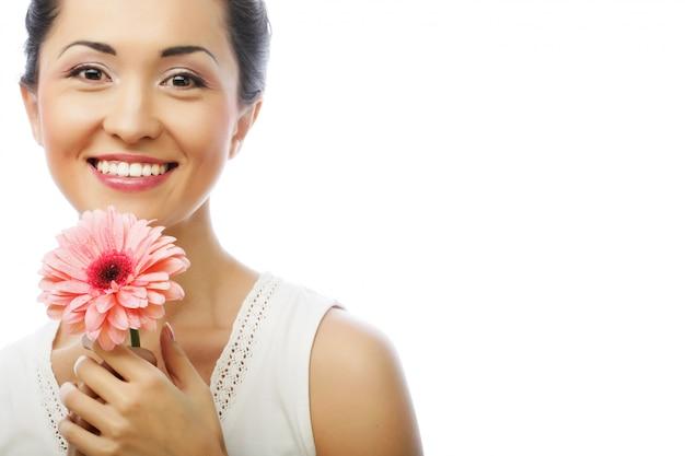 Donna asiatica felice che tiene una gerbera rosa