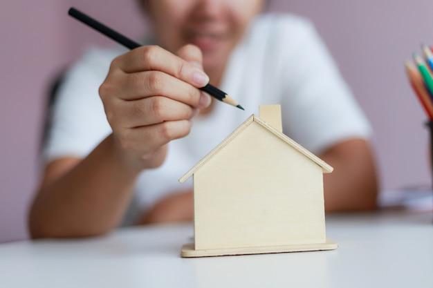 Donna asiatica felice che usando matita per disegnare con la progettazione e la decorazione di legno della metafora del porcellino salvadanaio della casa la profondità di campo bassa del fuoco selezionato della casa