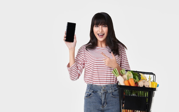 Donna asiatica felice con il canestro della tenuta dello smartphone in pieno delle drogherie della verdura fresca isolate su fondo bianco.