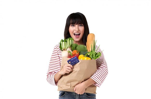 Donna asiatica felice con la carta di credito che giudica sacco di carta pieno delle drogherie della verdura fresca isolate su fondo bianco.