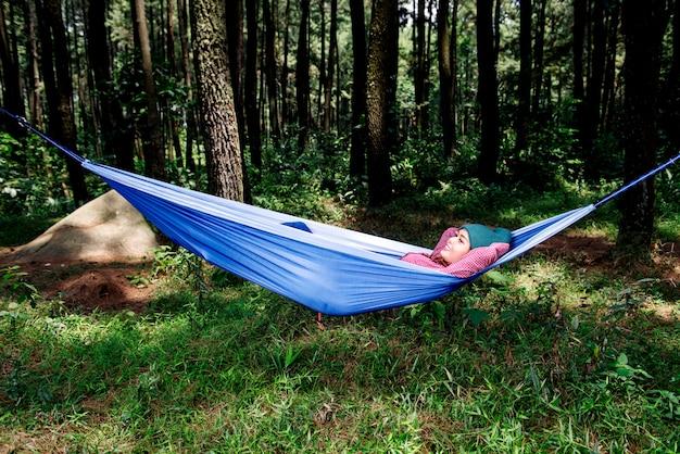 Donna asiatica felice del viaggiatore che si rilassa in amaca
