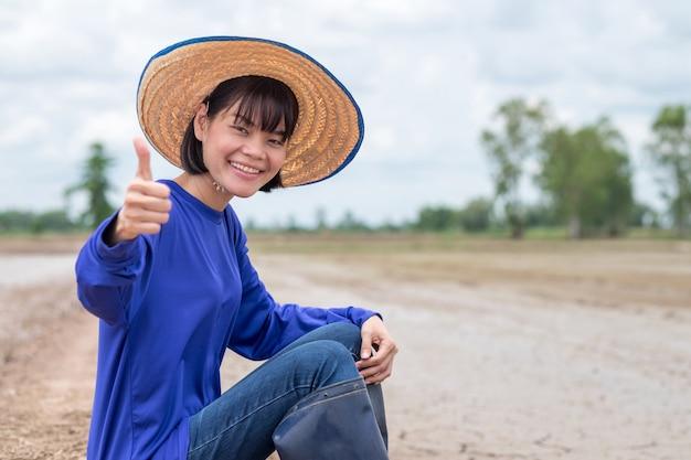 Donna asiatica felice dell'agricoltore che si siede e pollice sulla mano all'azienda agricola del riso