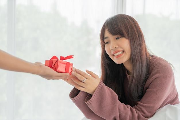 Donna asiatica felice di ricevere un contenitore di regalo