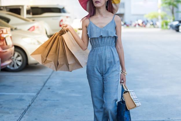 Donna asiatica felice in abito casual moda con borse della spesa e camminando nel parcheggio.