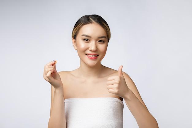 Donna asiatica felice in buona salute con l'isolato delle pillole isolato sopra fondo bianco.