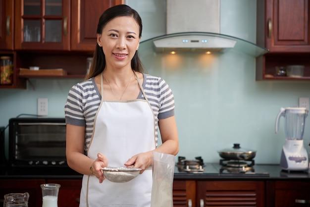 Donna asiatica felice nel setaccio della tenuta del grembiule con farina in cucina a casa