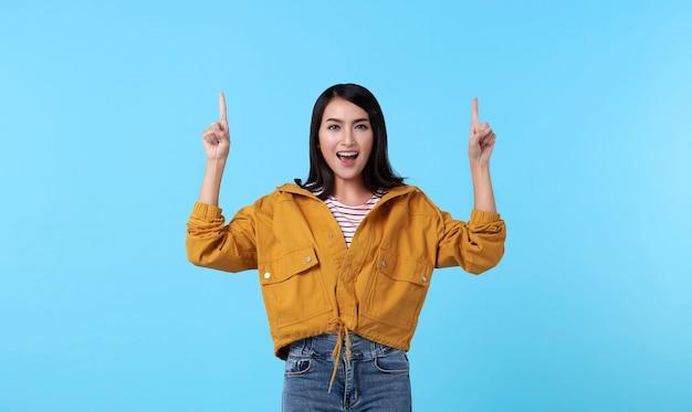 Donna asiatica felice sorridente con il suo indicare del dito isolata sul fondo blu-chiaro dell'insegna con lo spazio della copia.