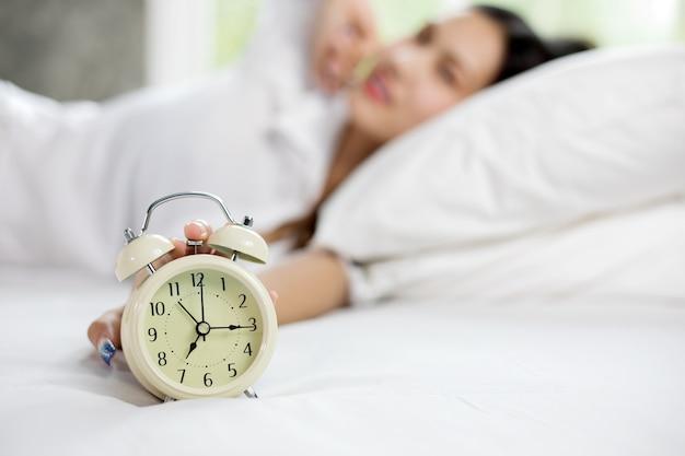 Donna asiatica felice sveglia e spegne la sveglia con una buona giornata
