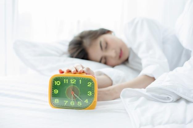 Donna asiatica felice svegliarsi e spegnere la sveglia con una buona giornata