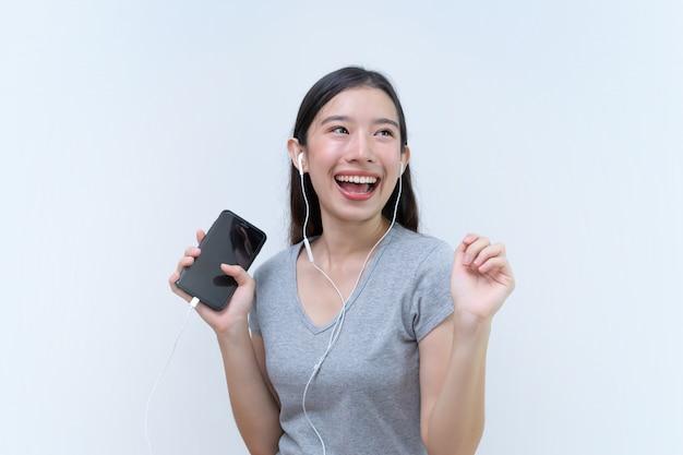 Donna asiatica godendo la canzone preferita e ballando, musica dal telefono cellulare