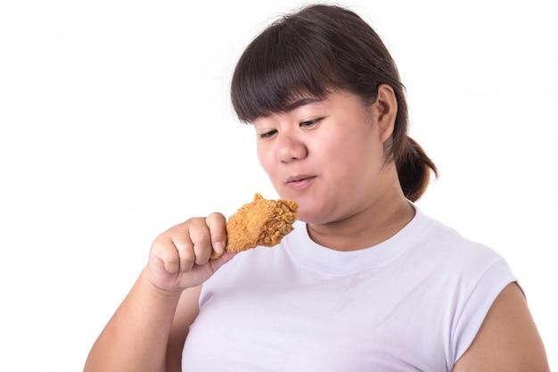 Donna asiatica grassa che tiene e che mangia pollo fritto isolato su bianco.