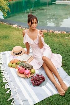 Donna asiatica graziosa che gode del picnic di estate su prato inglese verde vicino allo stagno.