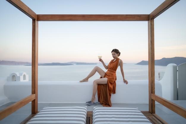 Donna asiatica in abito sexy con un bicchiere di vino godendo vista villaggio di oia nell'isola di santorini, in grecia.