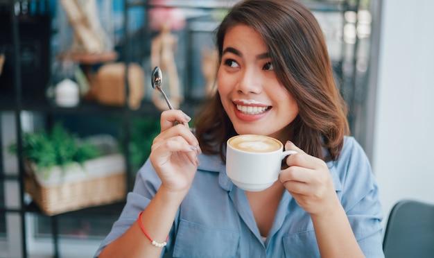 Donna asiatica in camicia blu nel caffè bevente del caffè e parlare con il sorriso dell'amico e il fronte felice