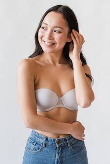 Donna asiatica in reggiseno e jeans
