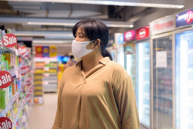 Donna asiatica in sovrappeso con shopping maschera dentro il supermercato