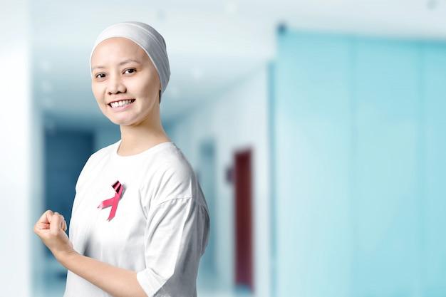 Donna asiatica in una camicia bianca con un nastro rosa in ospedale