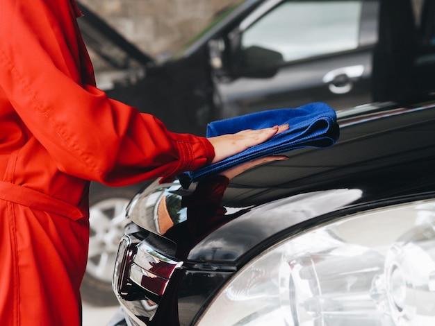 Donna asiatica in uniforme di ingegneria che controlla automobile nel garage